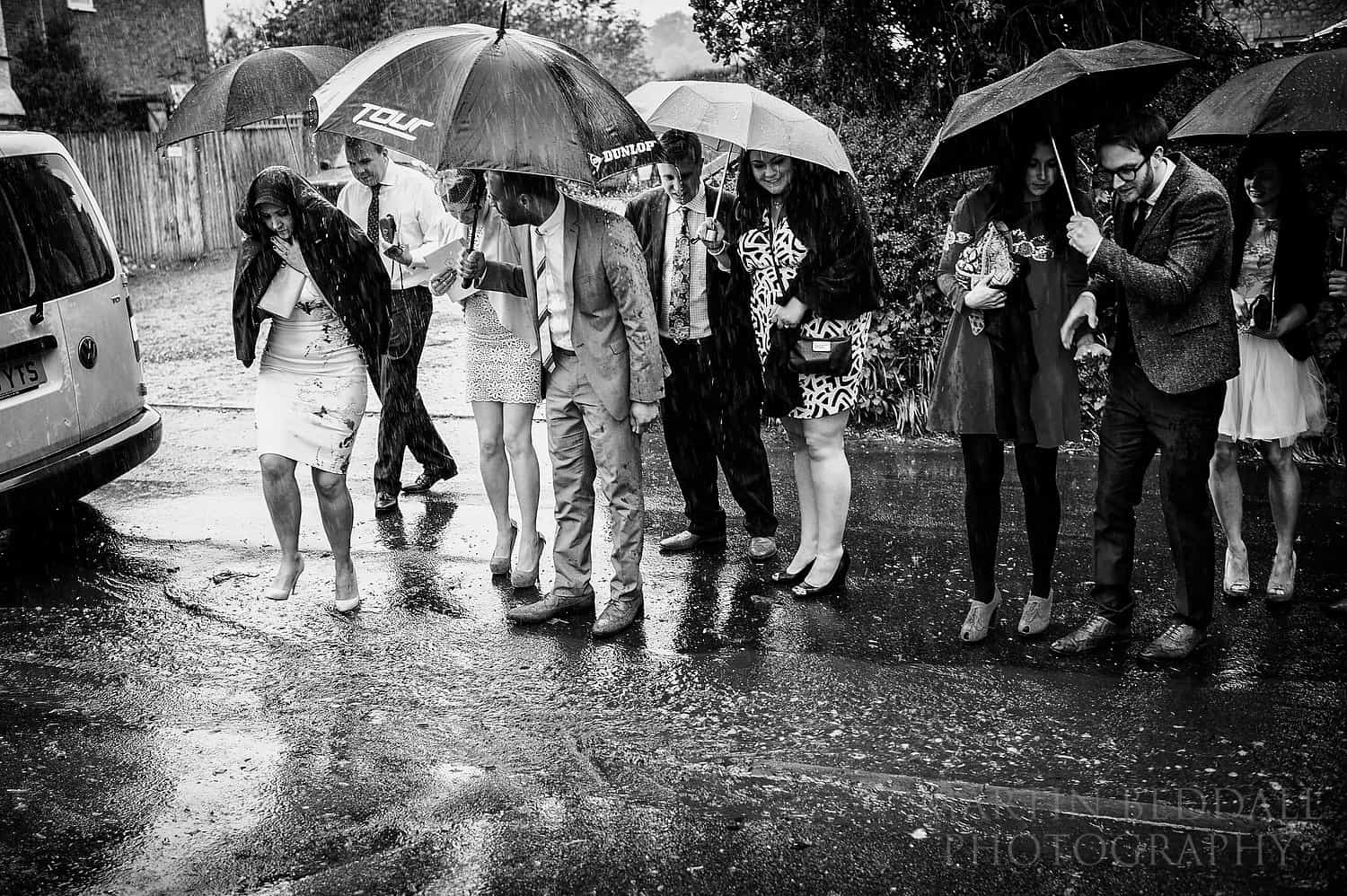 Wedding guests encounter a big rain puddle
