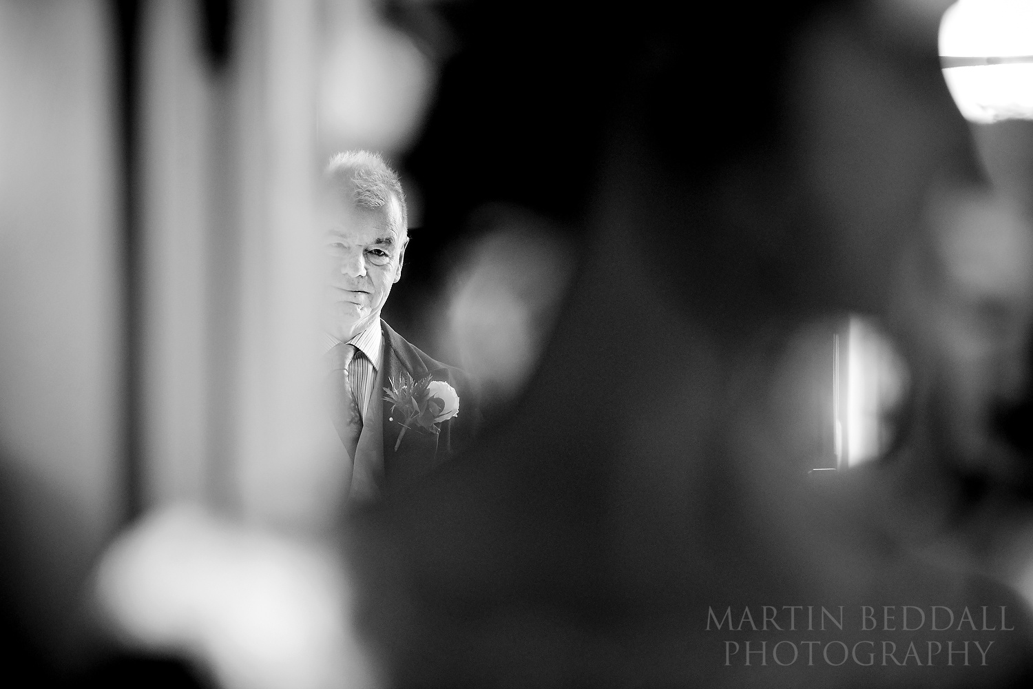 Father of the bride watches his daughter get ready