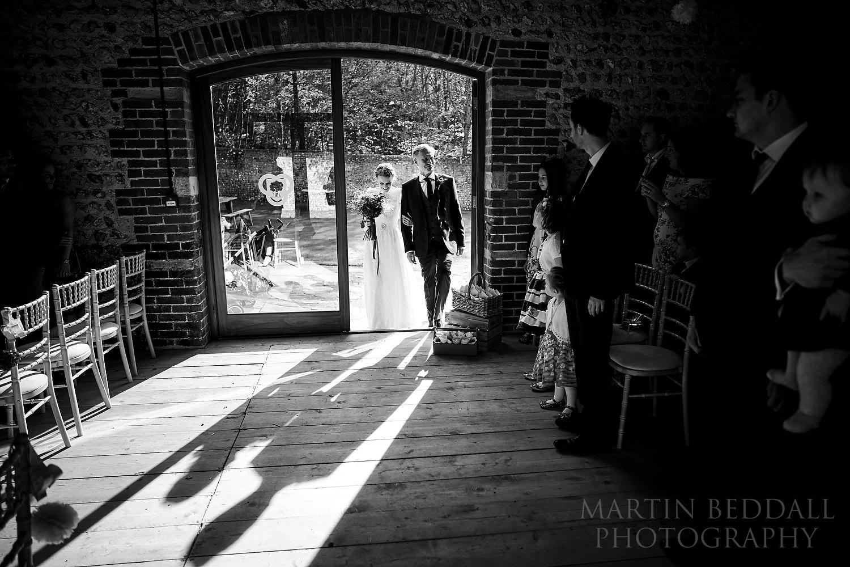 Father escorts the bride into Cissbury Barns wedding ceremony