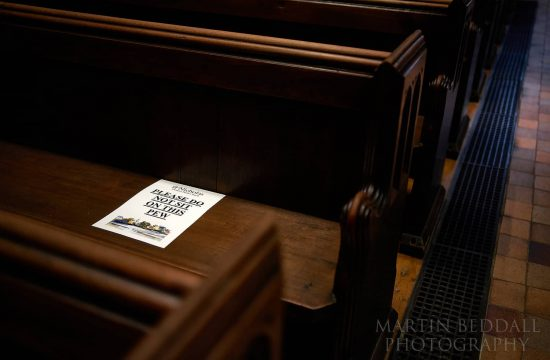 Notice on a church pew to conform with post-lockdown wedding regulations