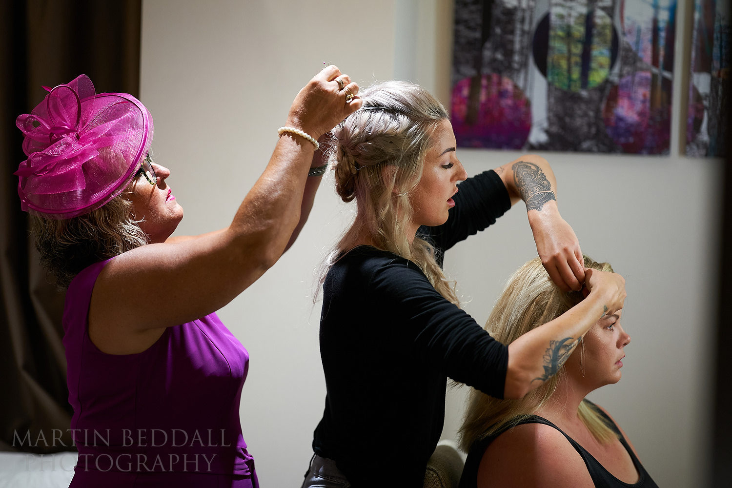 Mum adjusts bride's hair, bride adjusts the bridesmaid's hair