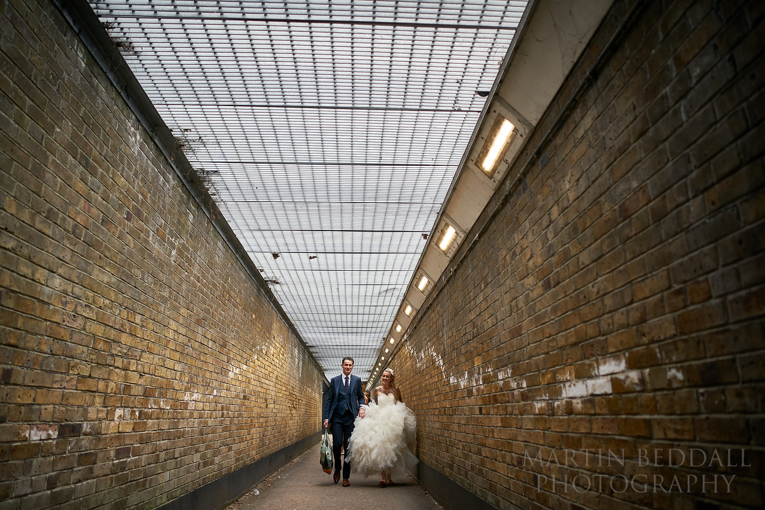 Bride and her father walking along the underpass in Chiswick