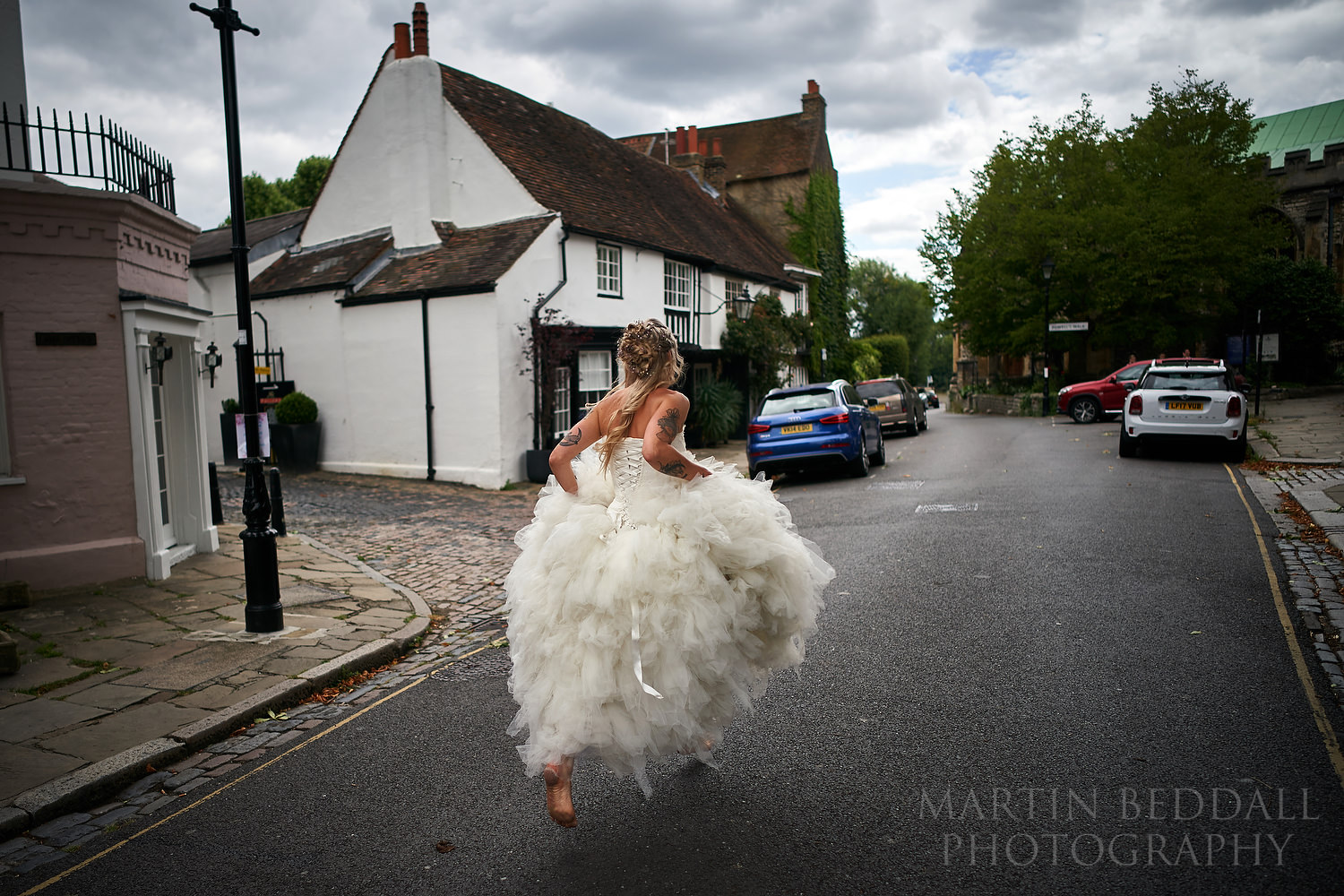 Running a bit late the bride starts to run to the church, barefoot.
