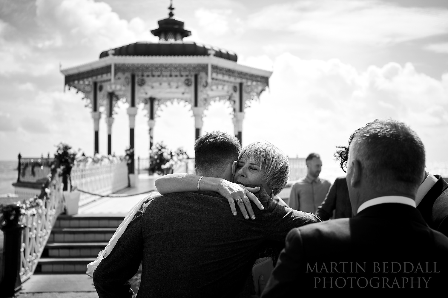 Groom hugs his mother at the Brighton bandstand