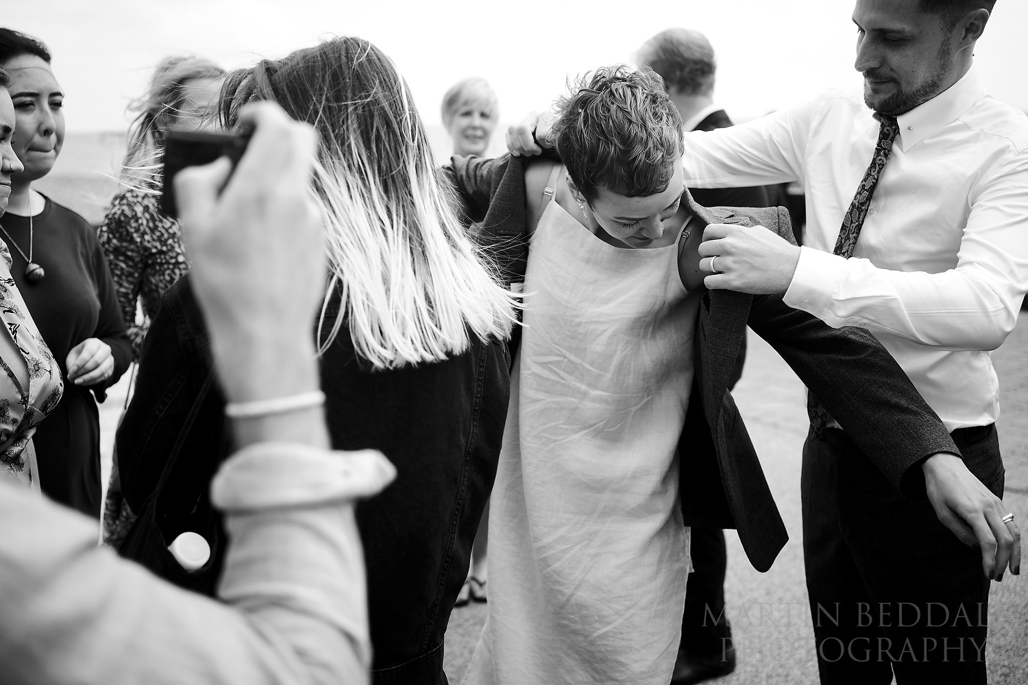 Groom offers his jacket to the bride