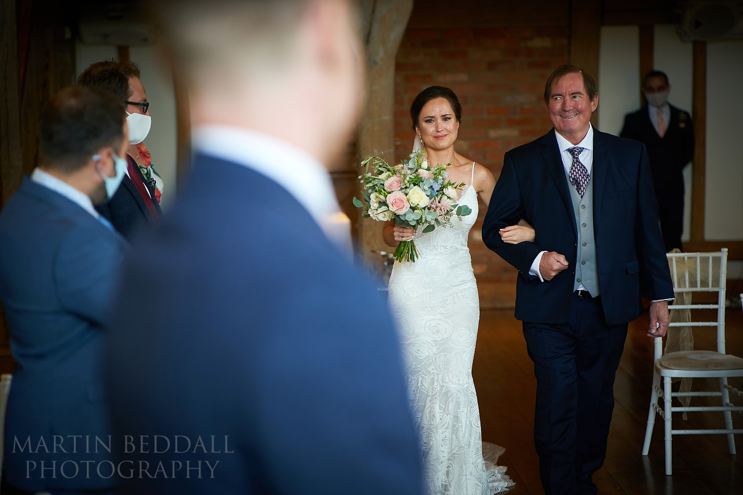 Emotional bride walks down the aisle with her father
