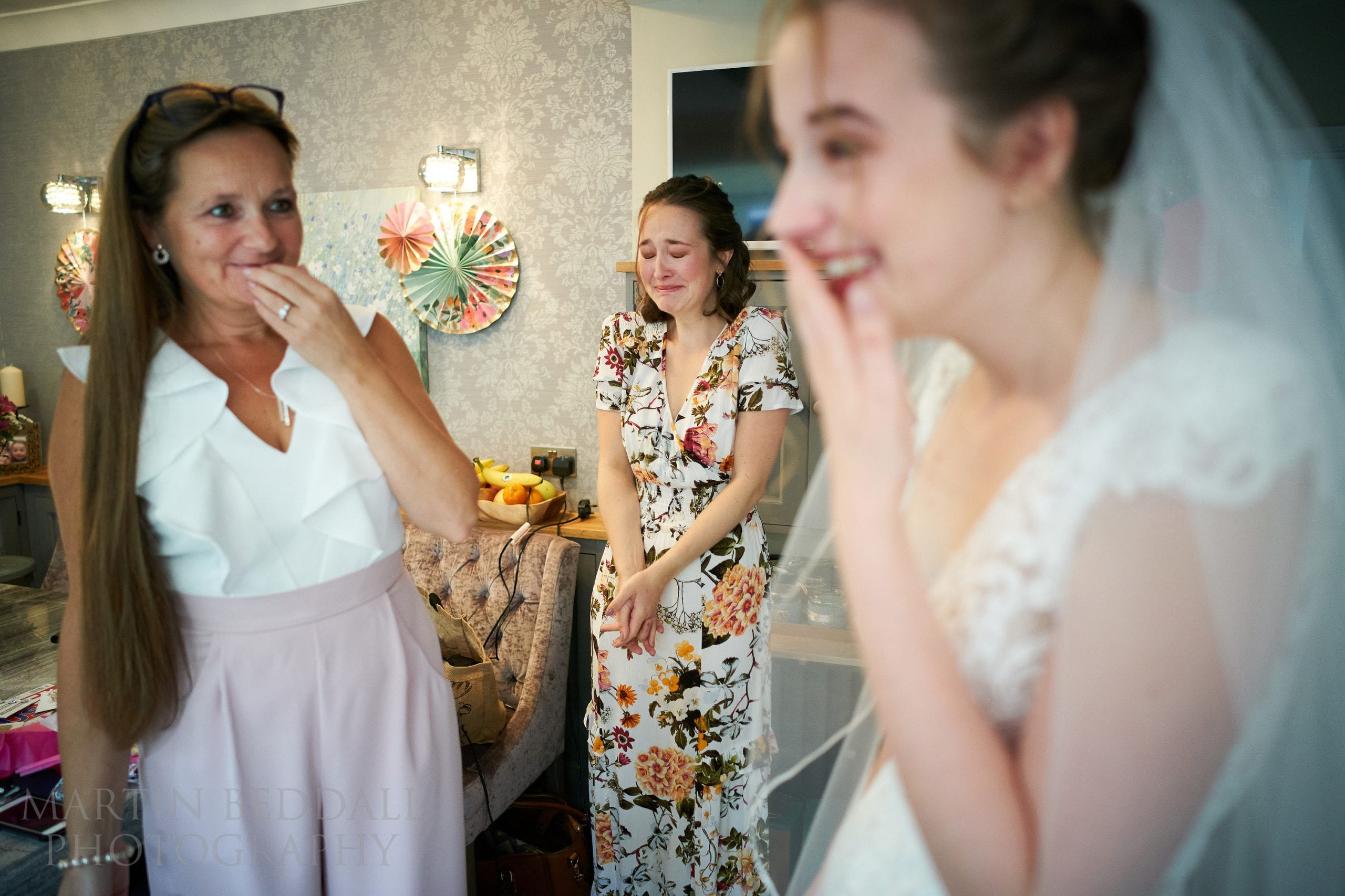 Reaction from mother and sister to bride in her wedding dress